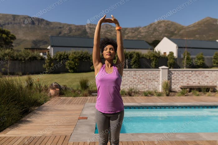 Young woman performing yoga next to the swimming pool in the backyard at home