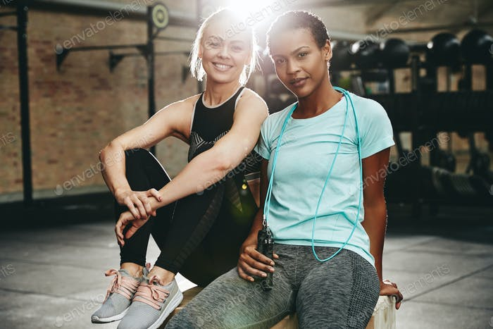 Smiling female friends sitting on a box after working out