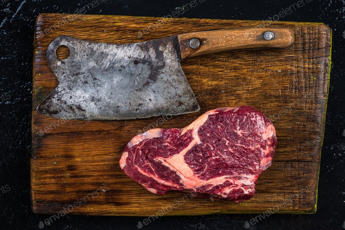 Butcher axe and piece of beef meat steak