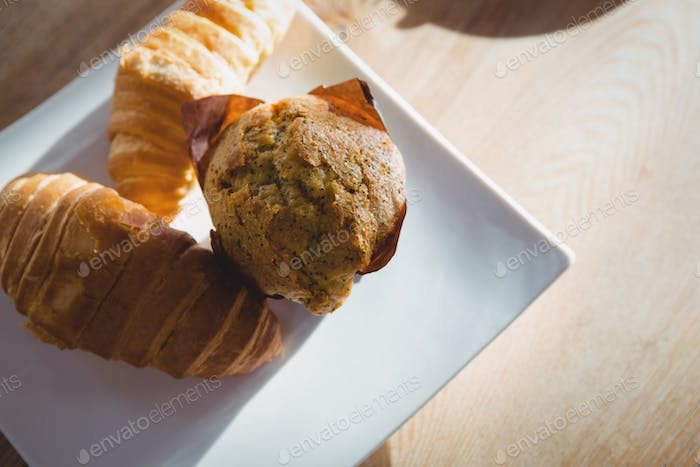 Muffin and croissants served in plate on table