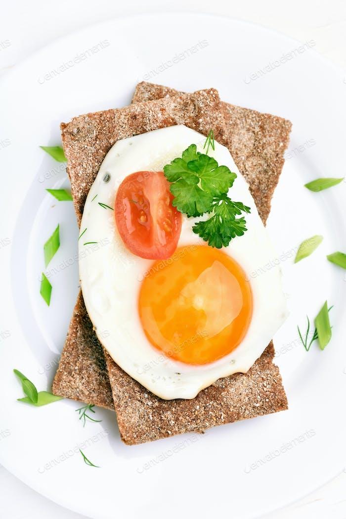 Fried egg, parsley and tomato slice on crispbread