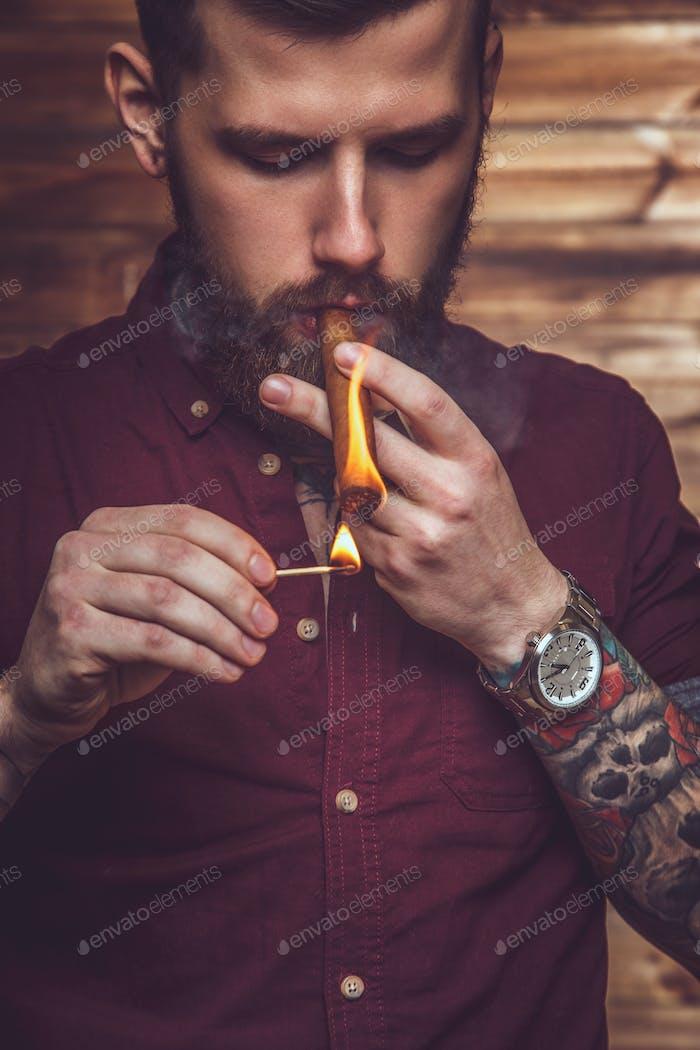 Berded man smoking cigar.