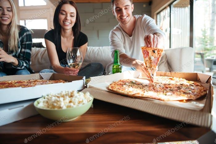 Freunde essen leckere Pizza zu Hause, während eine Party