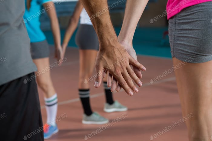 Mid section of volleyball players holding hands