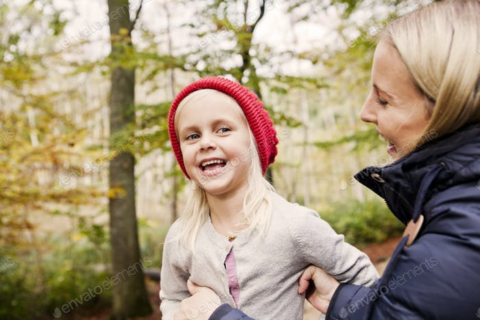 Happy girl looking at mother in forest