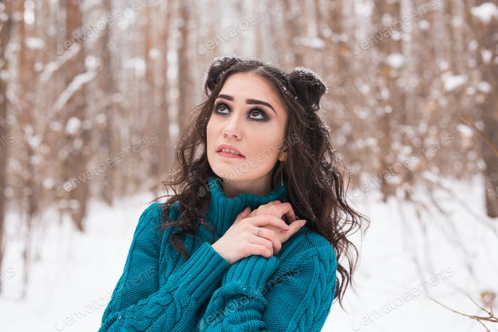 Portrait of young pretty woman walking in the winter snowy park