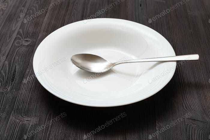 white deep plate with spoon on dark brown table