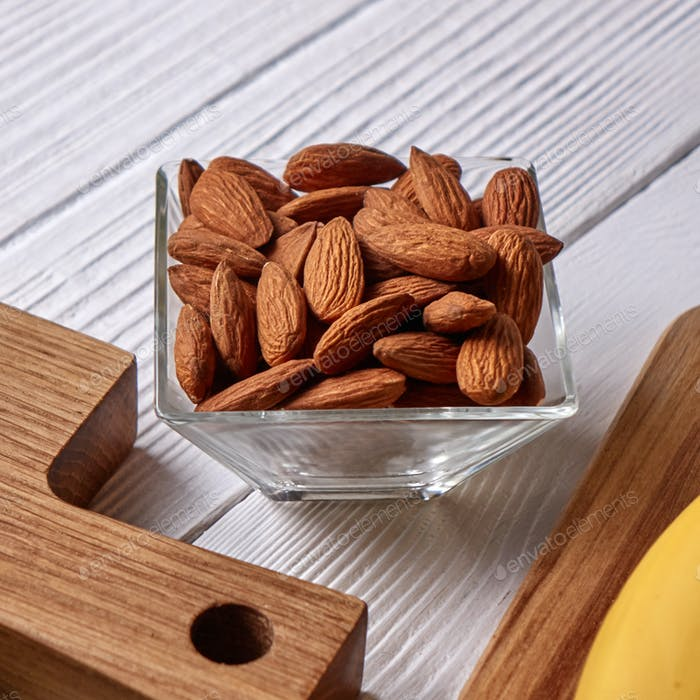 Close-up of almond nuts in a glass bowl on a wooden board on a gray wooden background. Vegetable