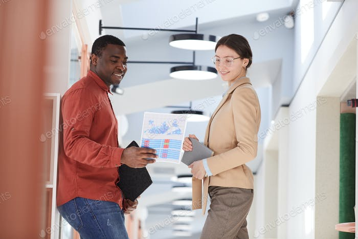 Cheerful Business People Discussing Documents in Modern Office