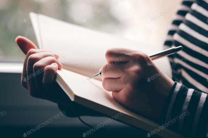 Left-handed woman writing diary
