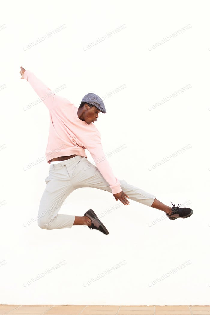 young african man jumping in air on sidewalk outdoors