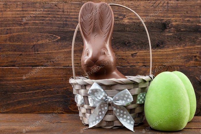 Schokolade Osterhase, Eier und Süßigkeiten auf rustikalem Hintergrund