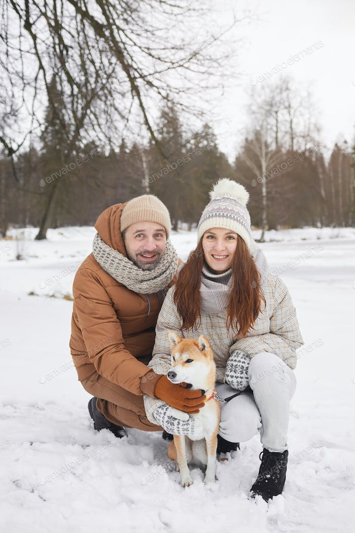 Smiling Couple Posing with Dog in Winter