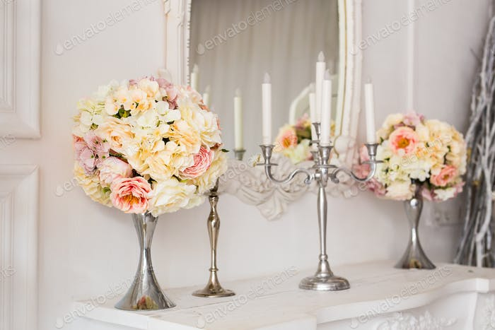 Bouquet on a fireplace with candle holders in a beautiful interior.