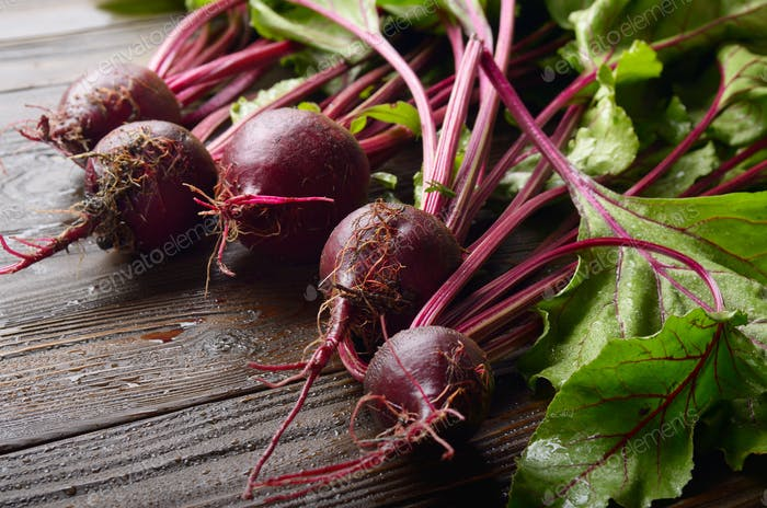 Fresh organic beetroots on kitchen wooden rustic table close up