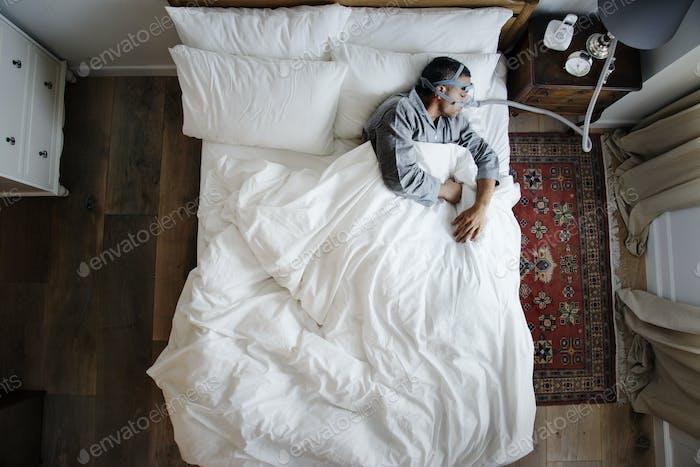 Mann schläft mit einer Anti-Schnarchen Maske auf