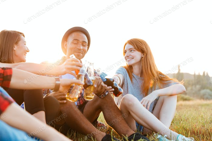 Group of happy young friends drinking beer and soda outdoors