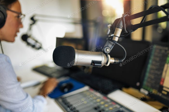 Microphone in a podcasting studio, host and the broadcasting equipment in the background