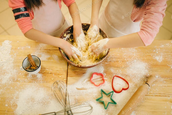 Two little girls chefs crumple the dough