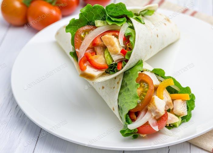 Tortilla Wraps mit gebratenem Hähnchenfilet, frischem Gemüse und Sauce auf weißem Teller