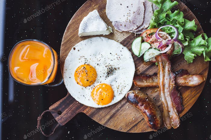 Breakfast with fried eggs, bacon and cheese camembert on wooden board