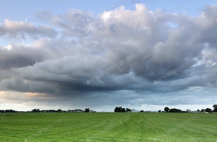 shower cloud over green meadow