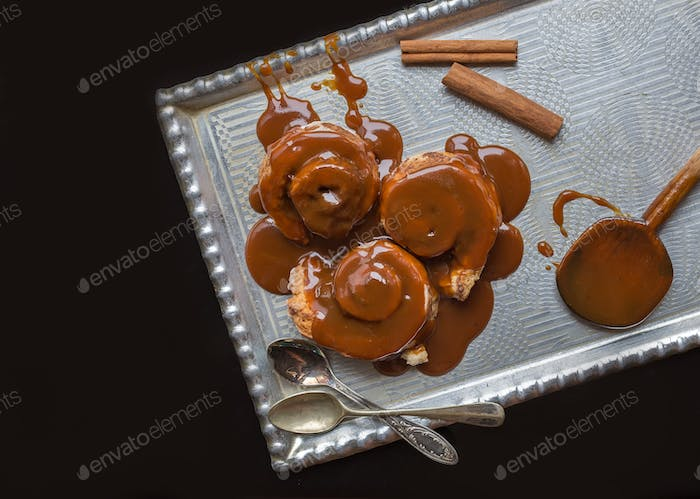 Cinnamon rolls with warm caramel topping and cinnamon sticks on