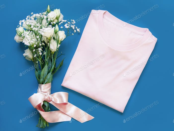 legen Sie es - gefaltetes T-Shirt in der Nähe von weißen Blumen platziert