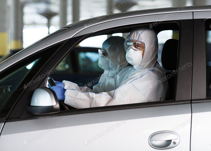 People in coronavirus protective suits driving a car