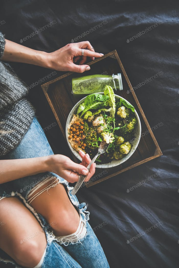 Healthy vegan bowl and smoothie and woman eating, top view