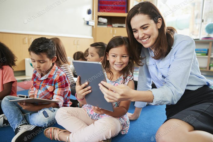 Teacher and girl in elementary class using tablet computers
