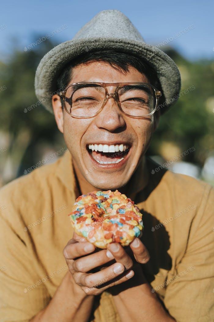 Happy man having a doughnut