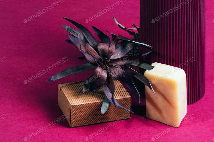 Piece of soap with ruffle carton box and dry flower on purple paper.
