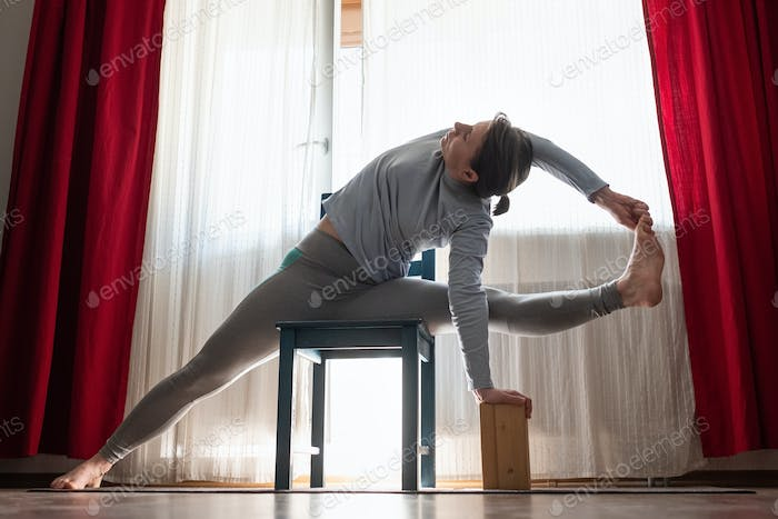 woman working out indoors, doing Vishvamitrasana Side bend Posture using chair.