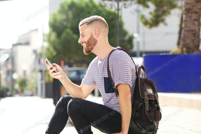 young man sitting outside looking at cellphone