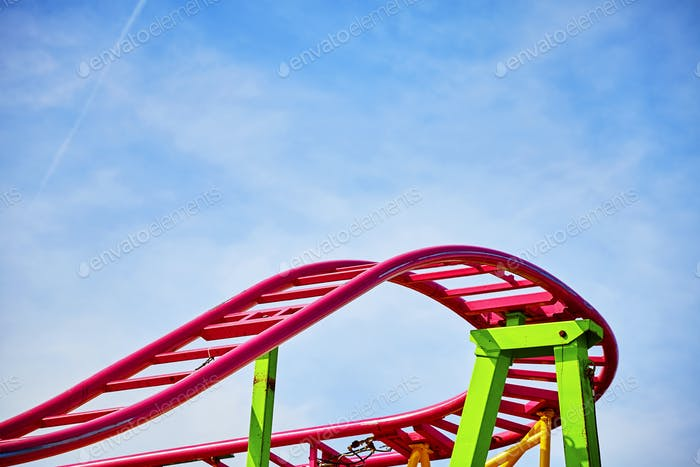 Roller coaster pink tracks in an amusement park.