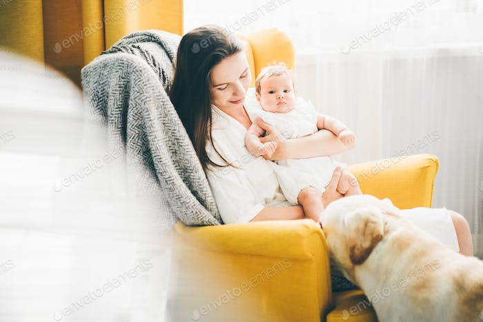 Beautiful young mother with a baby girl at home.