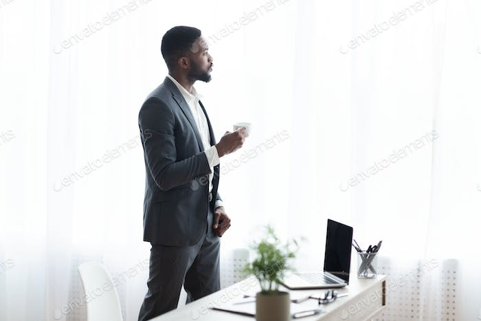 Pensive businessman standing near window in office and drinking coffee