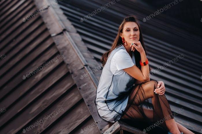 Ein Mädchen sitzt am Abend auf dem Dach eines Hauses in der Stadt. Porträt eines Modells in einem Kleid und