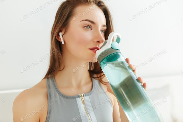 Young lady in sporty top dreamily lookingin aside with bottle of water and earphones on kitchen