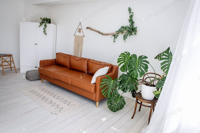 Stylish, trendy interior in Scandinavian style. In the white loft room there is brown leather sofa
