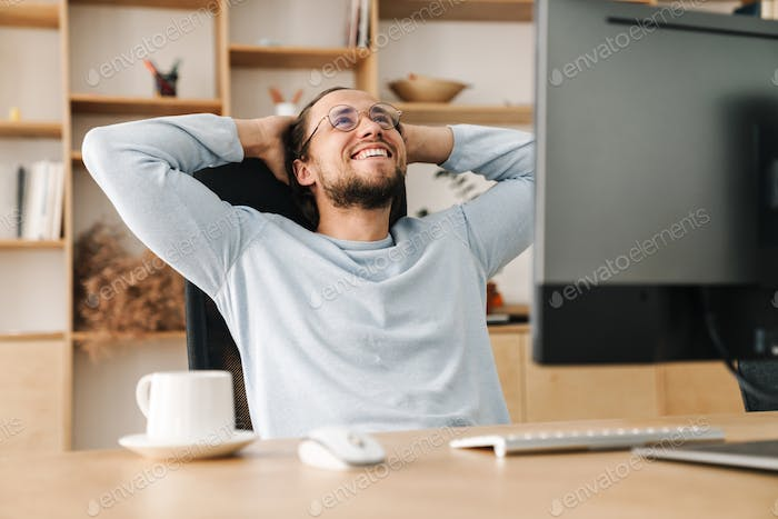 Image of joyful programmer man resting while working with computer