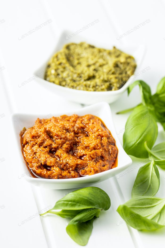 Green basil and red tomato pesto dip sauce  and basil leaves.