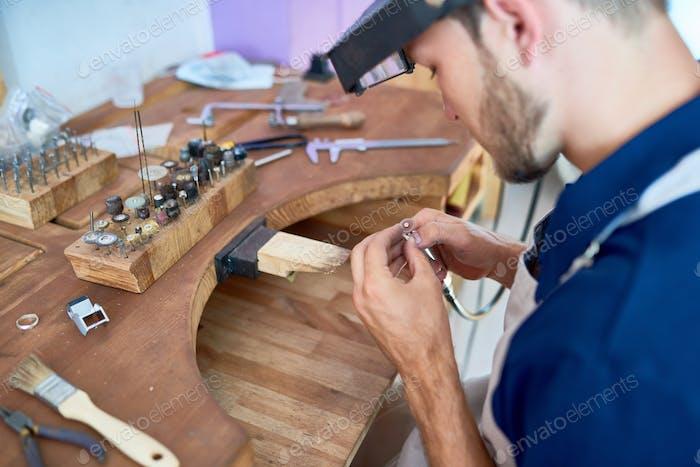 Craftsman Making  Jewelry in Workshop