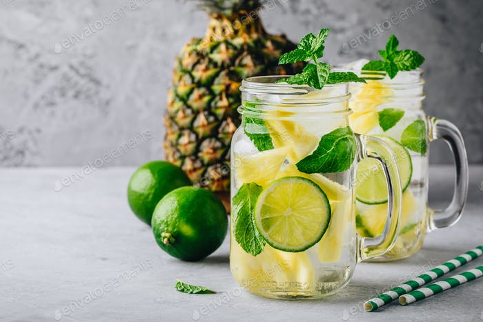 Infused detox water with pineapple, lime and mint. Ice cold summer cocktail or lemonade