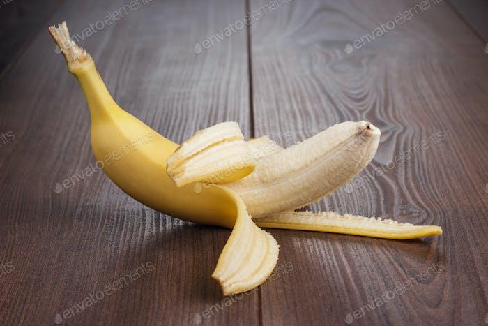 Fresh Peeled Banana On The Brown Background