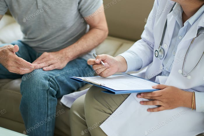 Doctor writing on clipboard during home visit