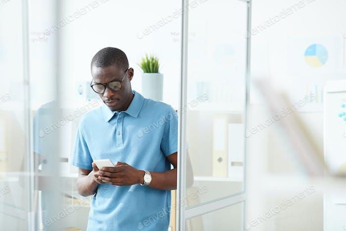 Afrikanische Büroangestellte mit Telefon für Online-Gespräche