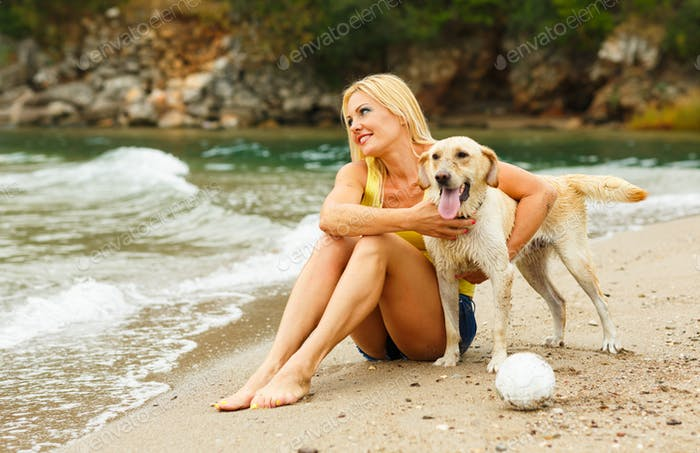 Woman with dog playing on the beach