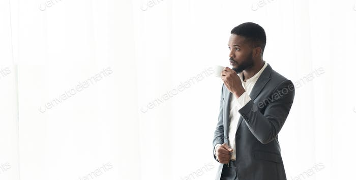 Pensive African American businessman enjoying cityview from window in office